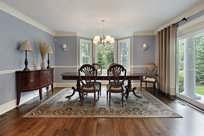 The charming dining room offers an oval dining table and ornate cushioned chairs that sit on a shabby chic rug over hardwood flooring.