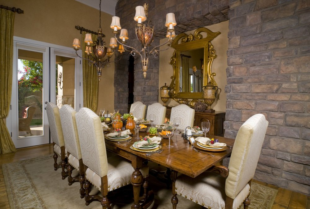 This dining room offers an elegant dining table and chairs set lighted by beautiful chandeliers.