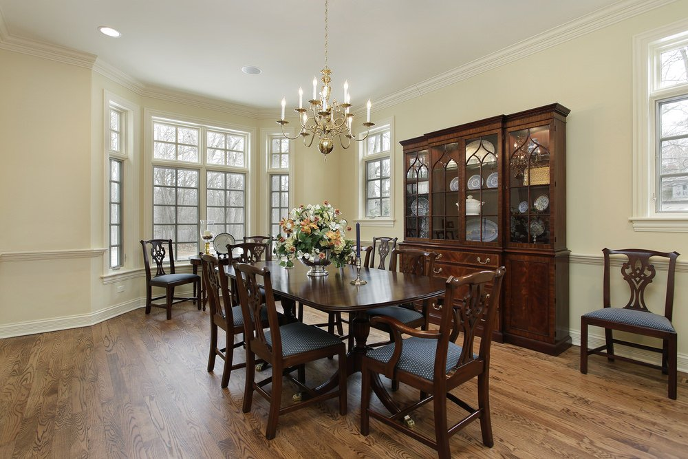 Classic dining room illuminated by a brass candle chandelier that hung over a wooden dining set topped with lovely centerpieces.