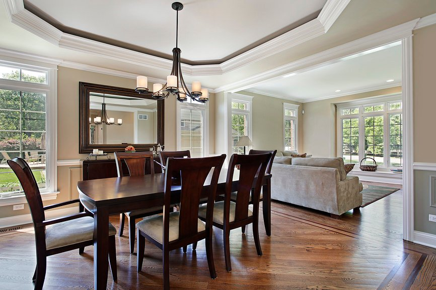 A classy dining room set lighted by a modish chandelier hanging on the tray ceiling.