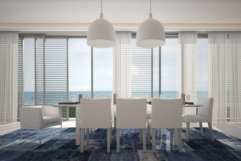 Natural light streams through the panoramic windows covered with white sheer curtains in this modern dining room. It has a white dining set that sits on a blue rug.