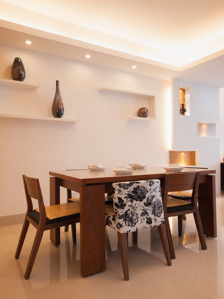 Clean white kitchen showcases floating shelves designed with modern decors and tray ceiling illuminated by strip and recessed lighting. It has a wooden rectangular table paired with cushioned dining chairs.