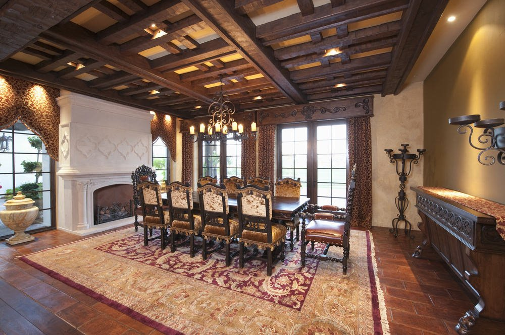 Classic dining room with terracotta flooring and full height windows covered with patterned draperies and valences. It includes a white fireplace and a wooden buffet table with a dining set in between.
