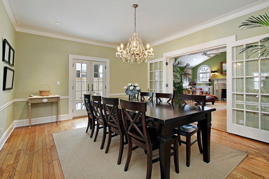 Traditional dining room with a french door fitted on the sage green walls and hardwood flooring topped with a gray rug. It includes a wooden dining set lighted by a crystal chandelier.