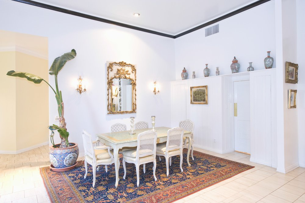 A tall potted plant creates a tropical feel in this dining room with a six-seater dining set and a patterned area rug that lays on the tiled flooring. It is decorated with ceramic vases and an ornate brass mirror flanked by candle sconces.