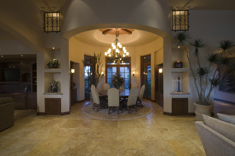 This dining room boasts an elegant-looking chandelier. The round dining table set is surrounded by wall lights.
