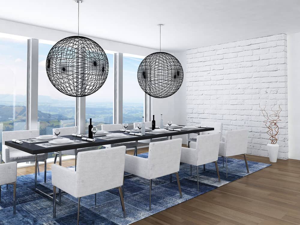 Modern dining room accented with oversized spherical pendants that hung over the black table and gray chairs. It has a white brick wall and hardwood flooring topped with a blue rug.