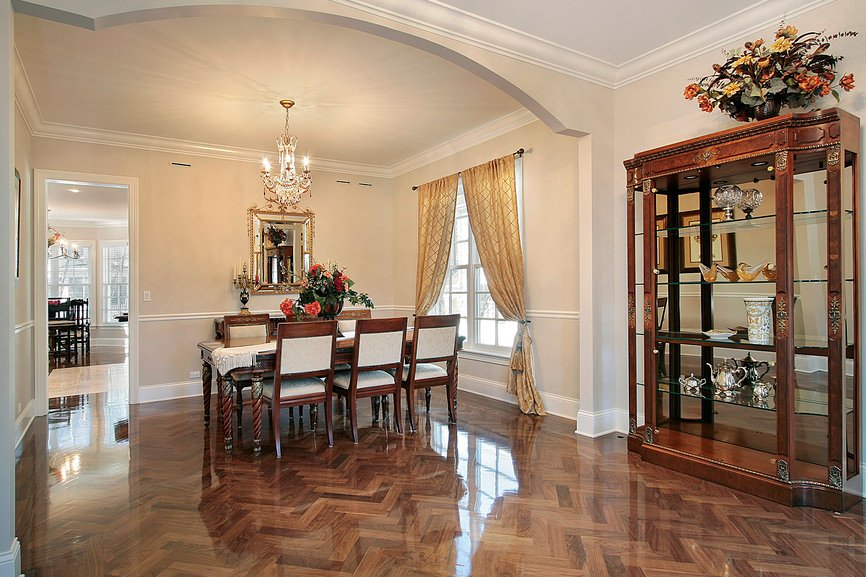 An expansive dining room accented with an arched wall and a glossy hardwood floor in herringbone pattern. It is lighted by a gorgeous chandelier that hung from the white ceiling.
