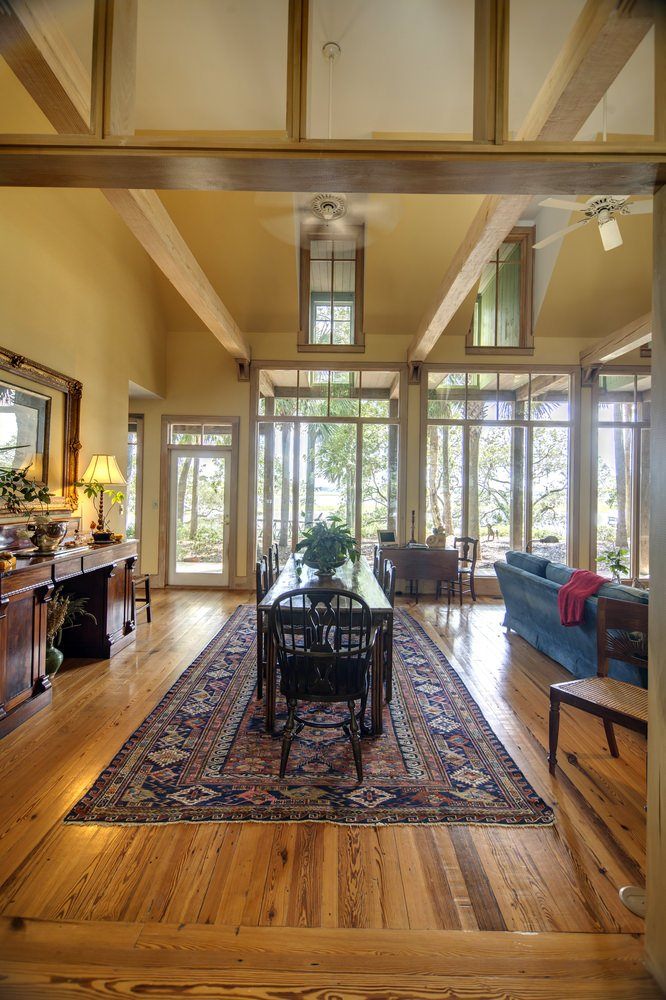 An open dining area showcases hardwood flooring and a high ceiling with exposed wood beams. It has a long dining table with black chairs that sit on a vintage rug.
