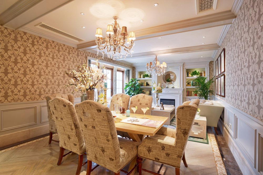 Formal dining room featuring elegant walls and chairs set on a large rug covering the tiles flooring and is lighted by a glamorous chandelier.