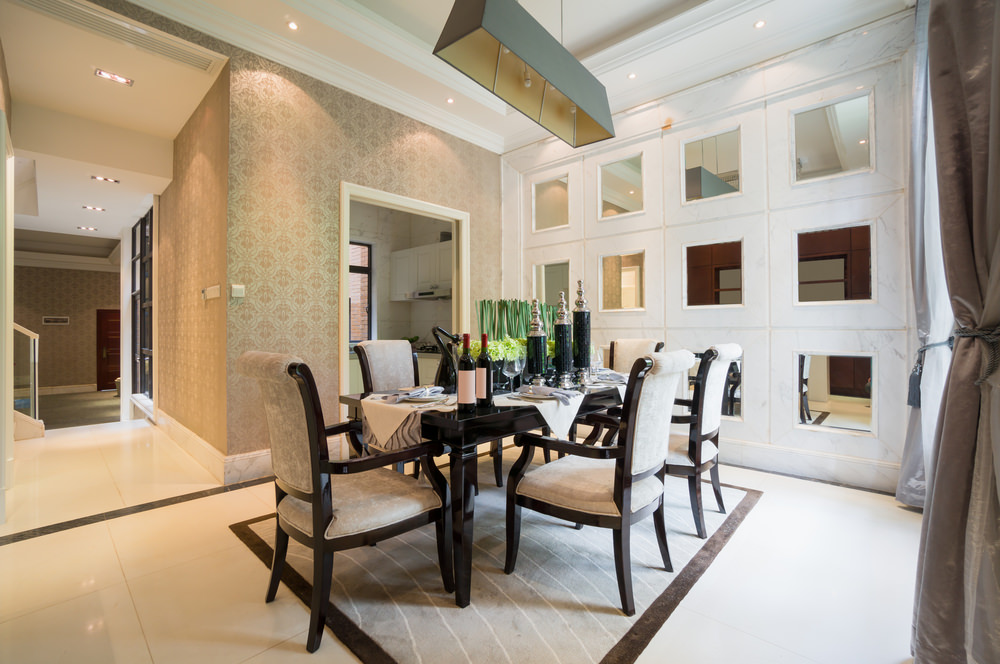 A classy dining room featuring attractive walls and high tray ceiling lighted by recessed ceiling lights.