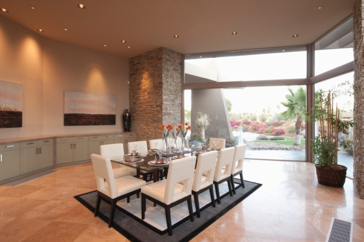 Spacious dining room features a glass top dining table and white modern chairs that sit on a black and white rug over tiled flooring.