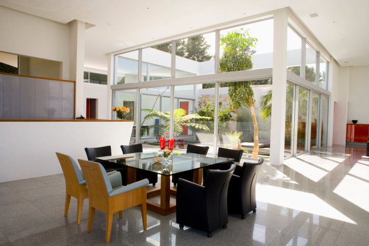 Large dining area featuring a glass top square dining table set with black and yellow chairs set on the home's tiles flooring.