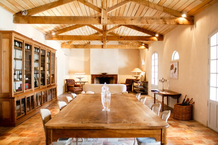 Large dining room featuring a large cabinetry and a rectangular dining table set, along with a small living space with a fireplace, all under the home's vaulted ceiling with exposed beams.