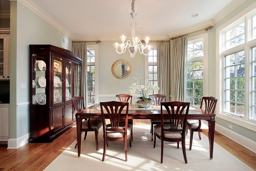 A fancy chandelier illuminates this dining room along with natural light that flows through the glass windows. It has a wooden dining set accompanied by a dinnerware display cabinet.