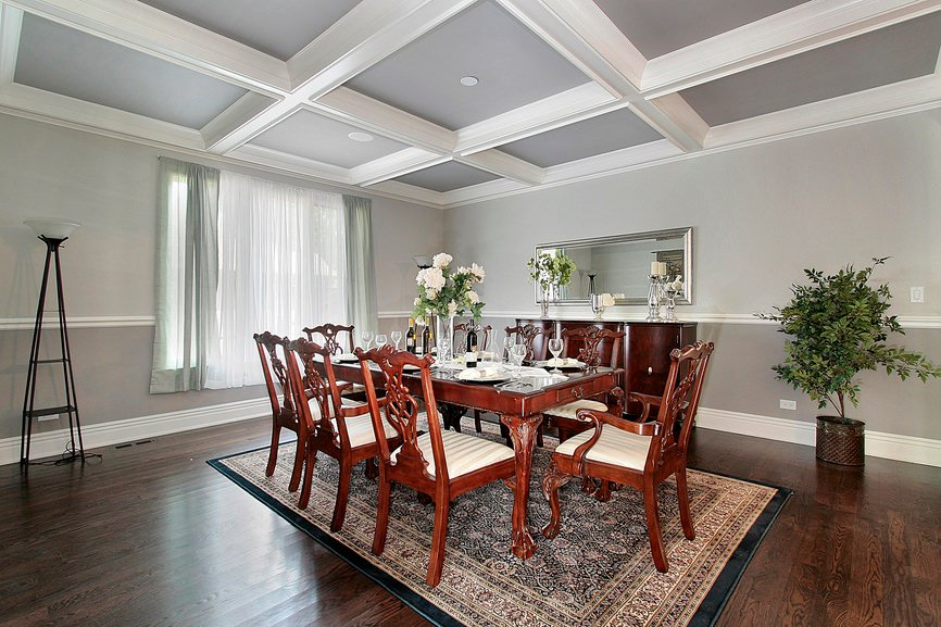 Sophisticated dining room with coffered ceiling and vintage rug over hardwood flooring. It includes a potted plant that brings life to the area.