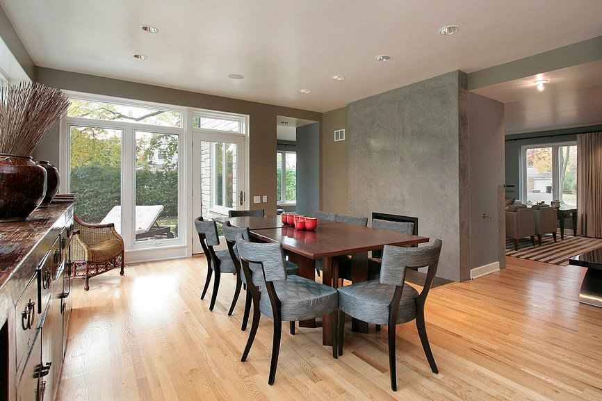 Airy dining room features a wooden dining table for eight and a rattan accent chair. There are sliding glass doors that bring the natural light in overlooking the green backyard.