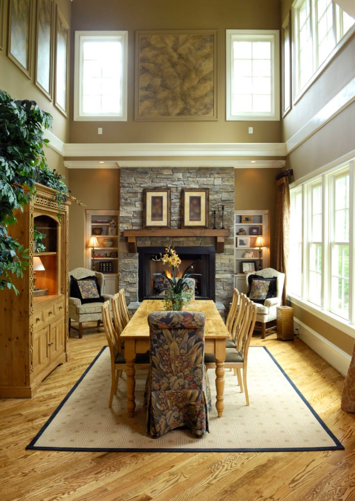 High ceiling dining room with moss green walls lined with white moldings. It includes a stone brick fireplace in between open shelving and wingback chairs.