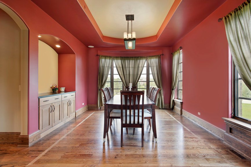 A dining room featuring hardwood floors and is surrounded by red walls. It also has a tray ceiling with a charming ceiling lighting.