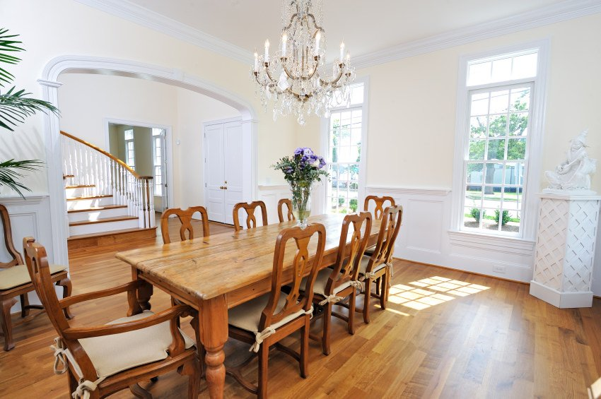 This dining room features a wooden dining set that complements with hardwood flooring. It is lighted by a gorgeous crystal chandelier that hung from the white ceiling lined with crown molding.