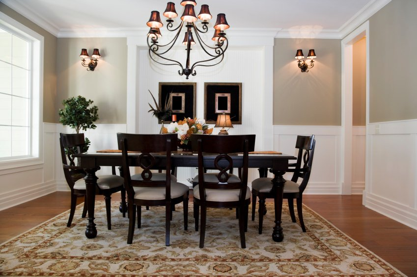 Elegant dining room accented with a fancy chandelier and matching wall sconces. It complements the dark wood dining set that sits on a vintage rug.
