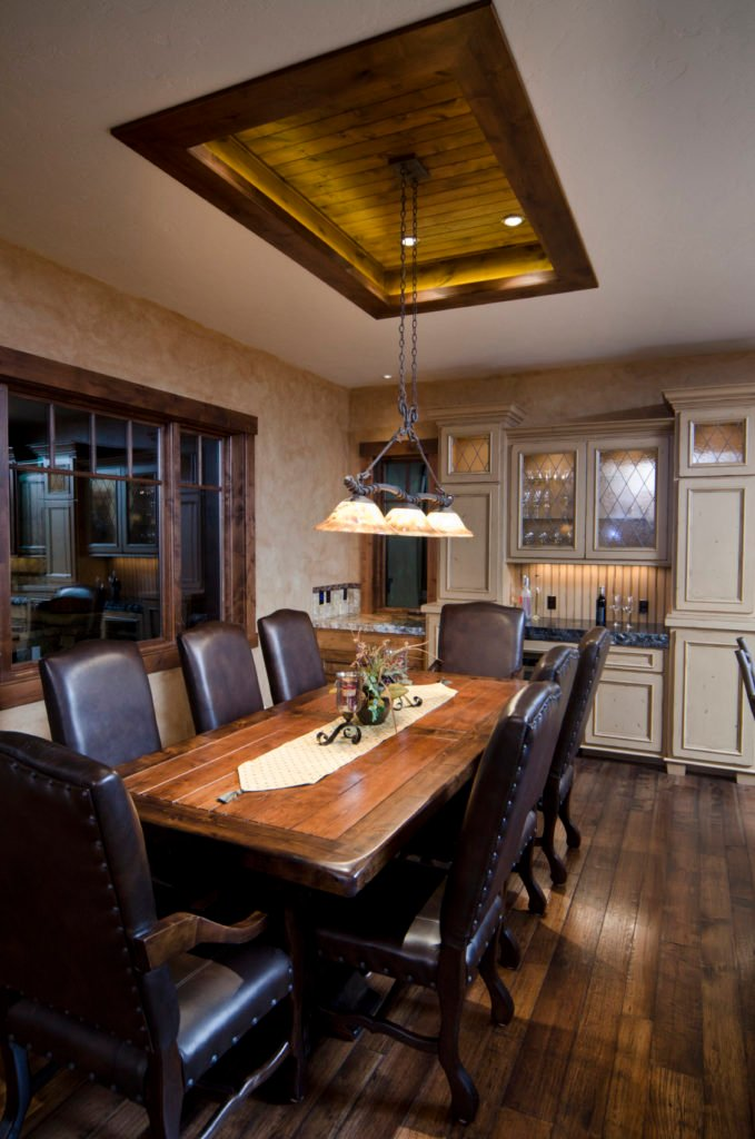 A dining room featuring hardwood flooring and a rustic tray ceiling. The dining table and chairs set is lighted by a fancy ceiling light.