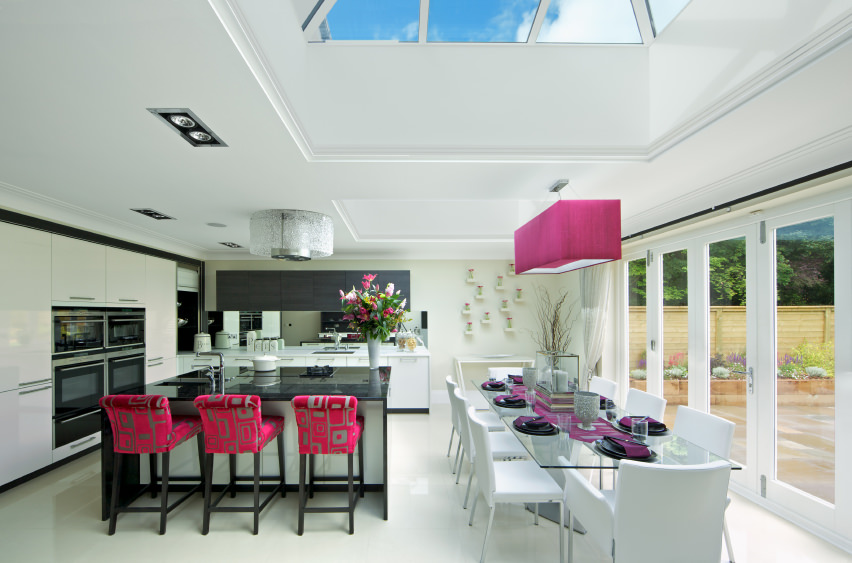 A dine-in kitchen featuring a very attractive dining table set and a breakfast bar with charming bar stools. The purple ceiling lighting looks so glamorous as well.