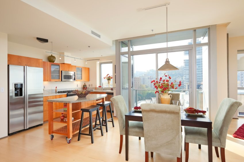 Eat-in kitchen boasts a floor to ceiling glass windows and light hardwood flooring. It includes a square dining table surrounded with gray velvet chairs and illuminated by a pendant light.