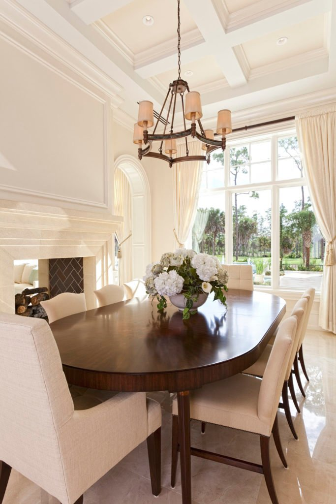 White dining room contrasted with a dark wood dining table that's surrounded with white upholstered chairs over tiled flooring. It is lighted by a classic chandelier that hung from the coffered ceiling.