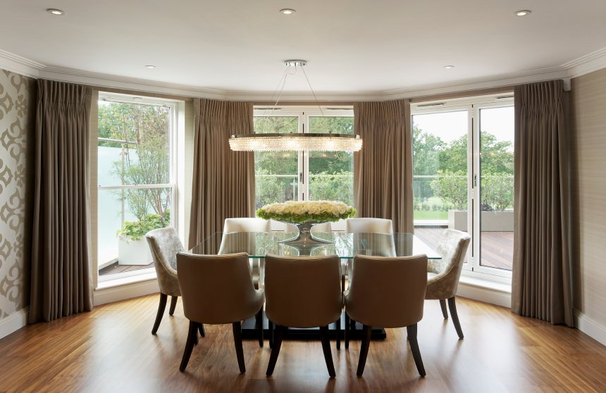 Sophisticated dining room with floor to ceiling glass windows covered with taupe draperies. It has a glass top dining table paired with white and gray chairs over hardwood flooring.