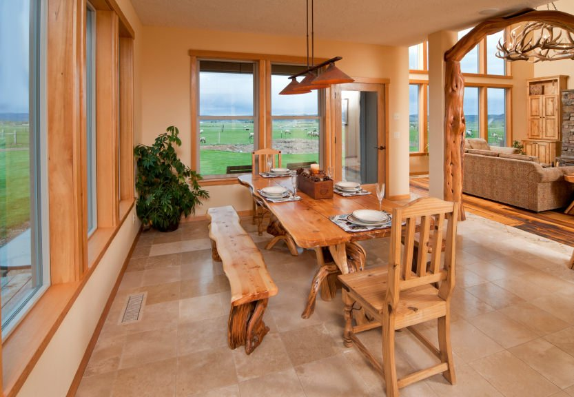 A warm dining room with tree stump dining table paired with matching benches and chairs. It has marble tiled flooring and glass windows overlooking a serene outdoor view.