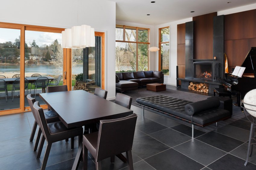 An open dining area offers a dark brown dining set that sits on black tiled flooring. It is illuminated by white pendants and natural light from the glazed windows.