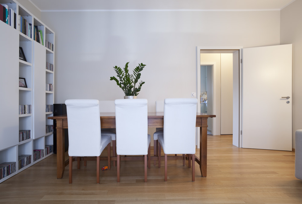 A dining room with wooden dining table and white chairs matching the white walls and white multiple shelves.