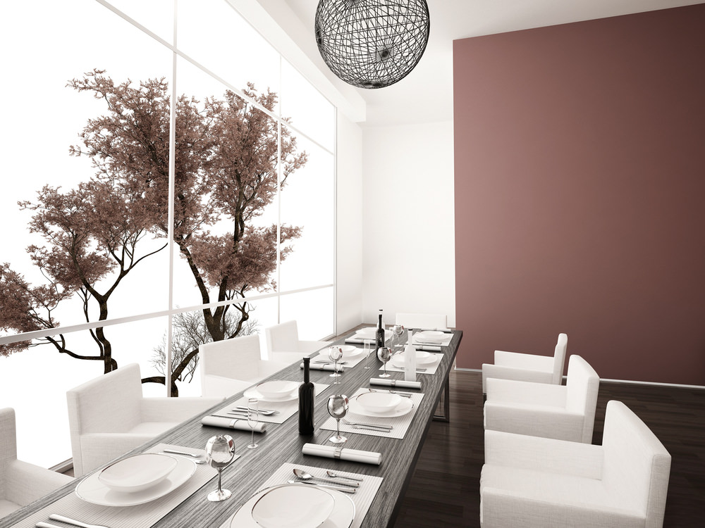 Modern dining room offers a lengthy wood dining table with white chairs over hardwood flooring.