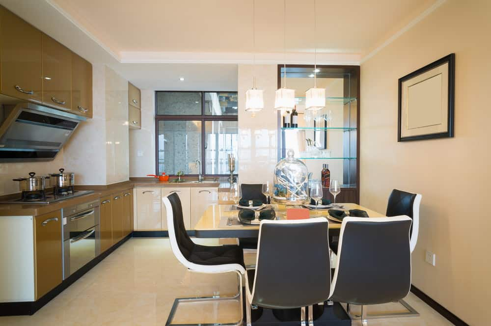 Three pendant lights illuminate this small dining space featuring modern black chairs surrounding a glossy dining table.