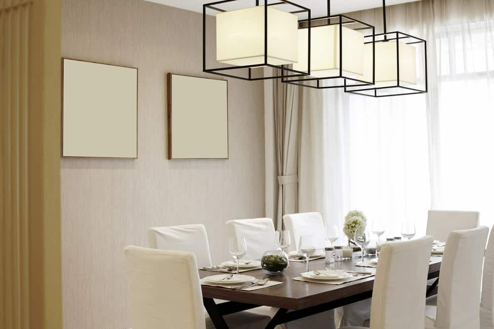 Neutral dining room decorated with a pair of blank canvas wall arts and large square pendants that hung over a wooden dining table and white skirted chairs.