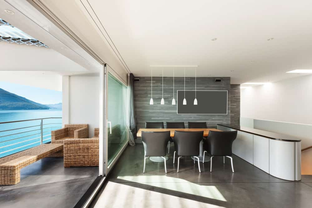 Dining area with concrete flooring and gray wall fitted with a display panel. It has a wooden dining table paired with black modern chairs and white pendants.