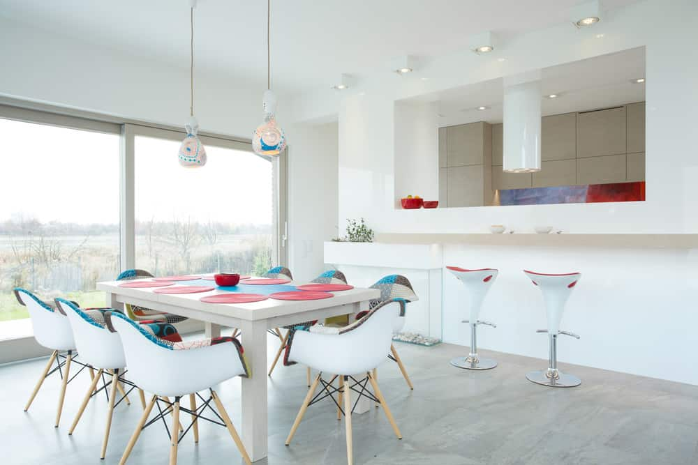 A pair of lovely white pendants hang over the charming dining set topped with red and blue mats. It has glass windows that bring natural light in.