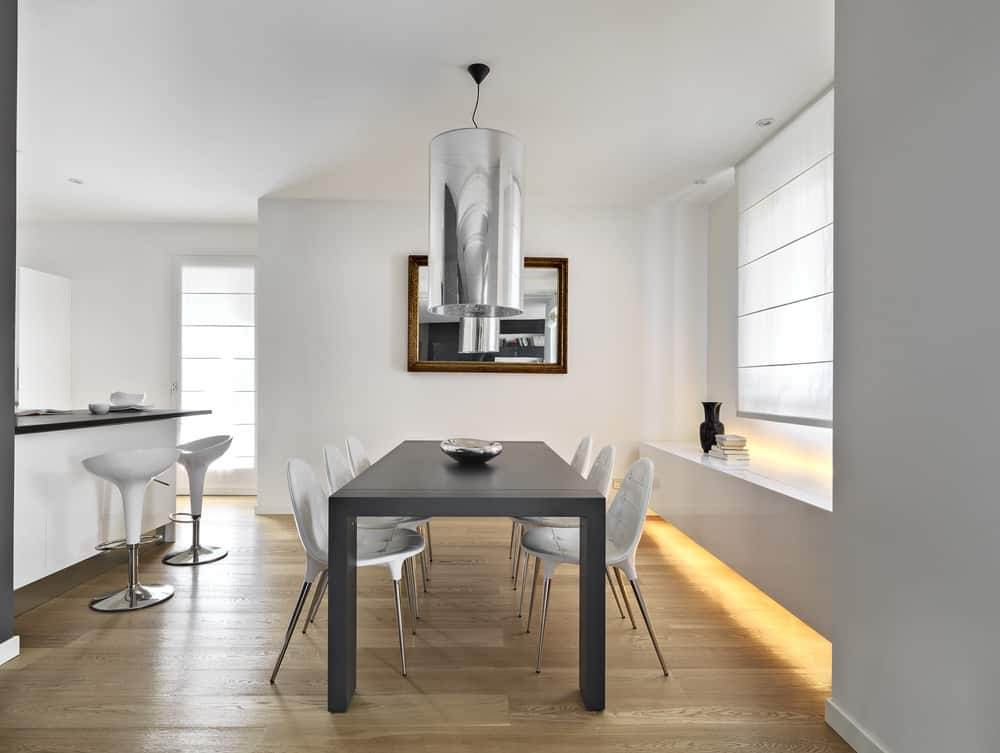 White dining room offers a sleek floating table across the gray dining table with modern chairs illuminated by a cylindrical pendant light.