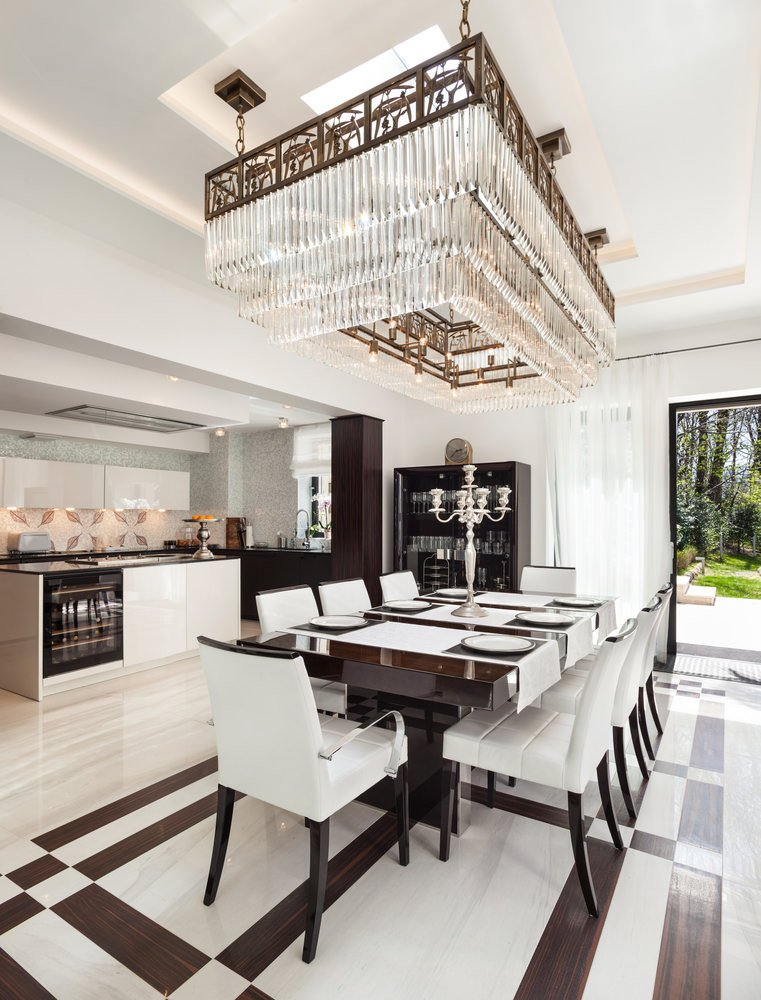 A dine-in kitchen featuring very stylish flooring that matches the dining table and chairs set. It has a breathtaking ceiling lighting above it.