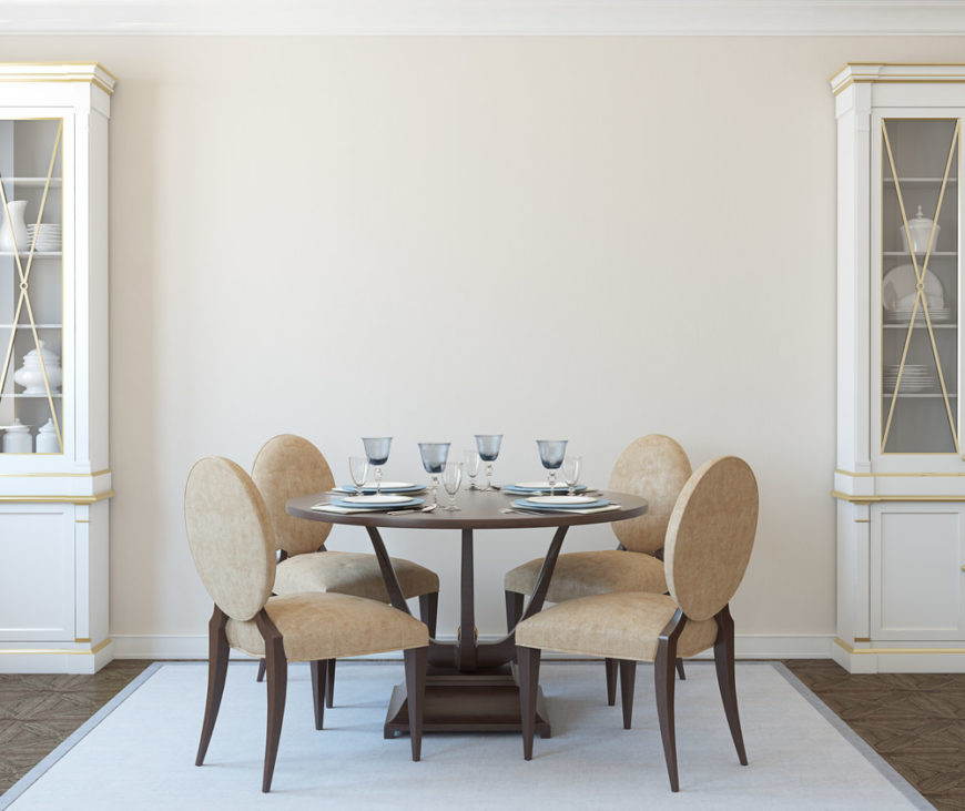 A round dining table set with classy seats set on the rug covering the elegant-looking flooring.