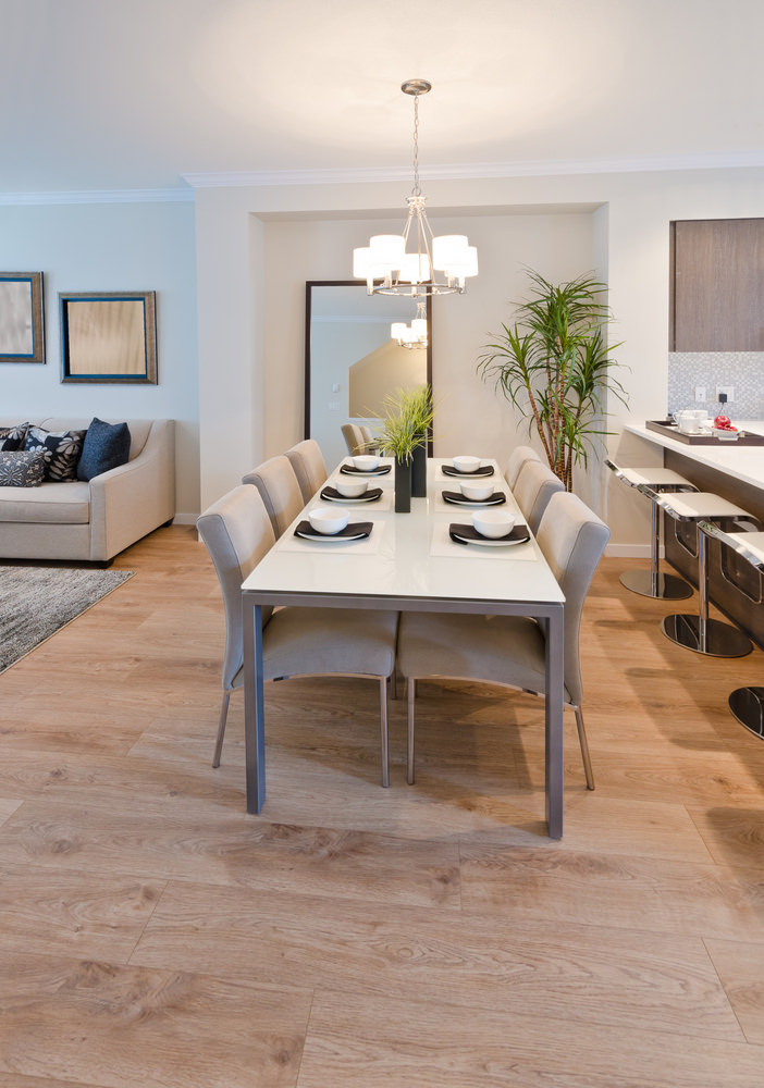 Neutral dining area accented with indoor plants that bring color and life to the room. It has a metal dining table and beige upholstered chairs over natural hardwood flooring.