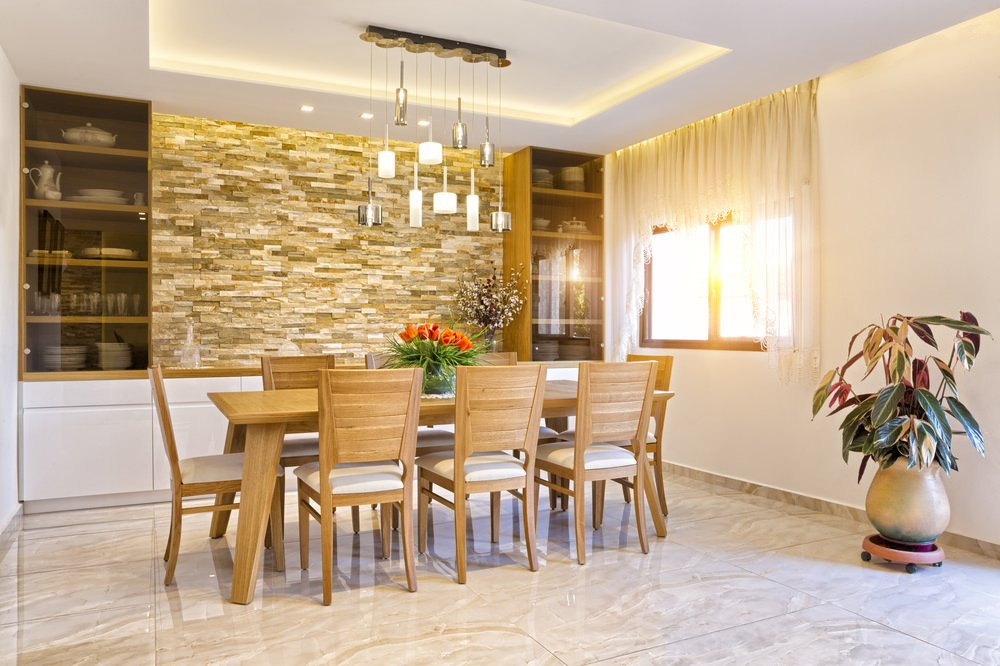 A formal dining room featuring classy tiles flooring and a stunning tray ceiling with beautiful pendant lights just above the table and chairs set.