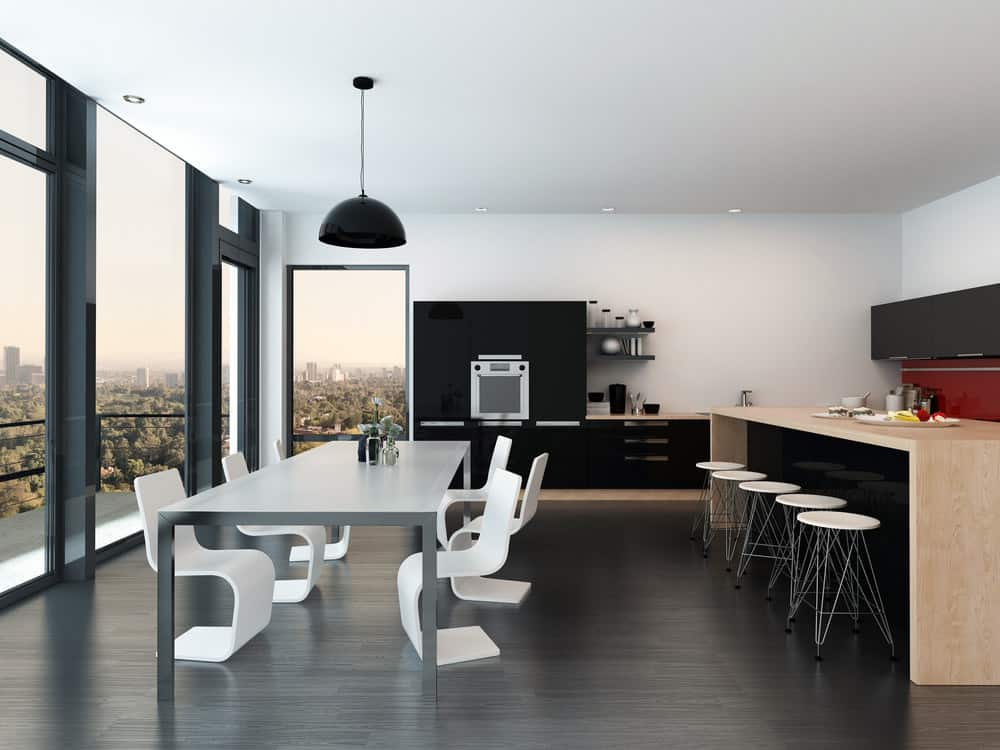 Modern dining room with dark hardwood flooring and glass paneled windows. It includes a metal dining table paired with white sleek chairs and lighted by a black dome pendant.
