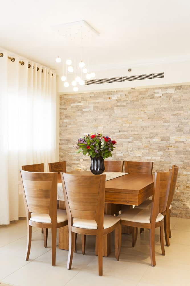 This dining area boasts a bubble pendant light that hung over the wooden dining set. It has a stone brick wall and glass window covered with white grommet drapery.