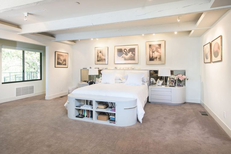 A large master bedroom with a bed featuring built-in shelving at the edge. The room offers carpet flooring and white walls featuring attractive wall decors.