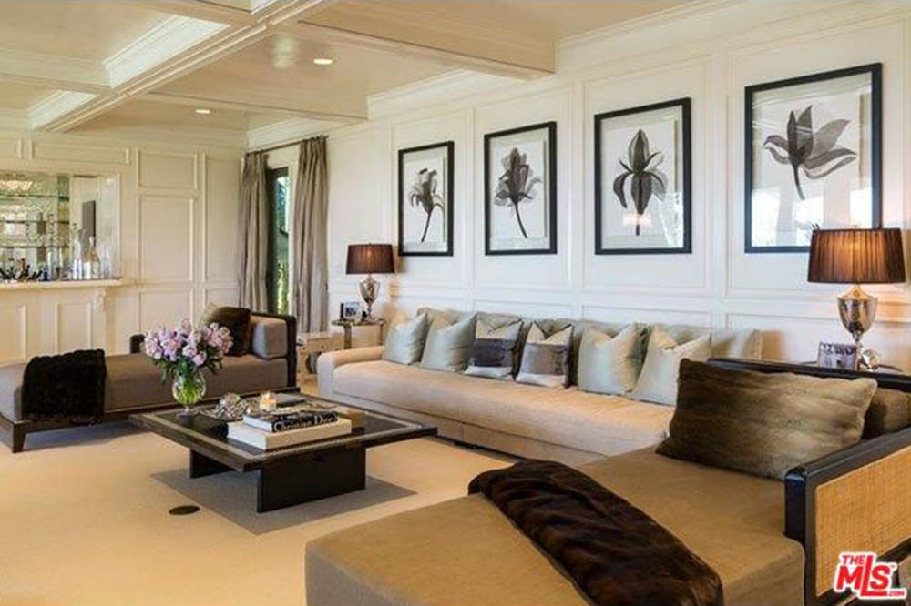 Formal living room decorated with a series of floral wall arts mounted on the white wainscoting that complements with the coffered ceiling.