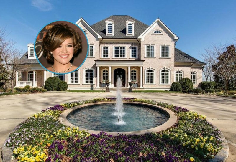 A gorgeous view of Kelly Clarkson's Tennessee Lake Mansion showcasing the beautiful fountain in the center of the courtyard.