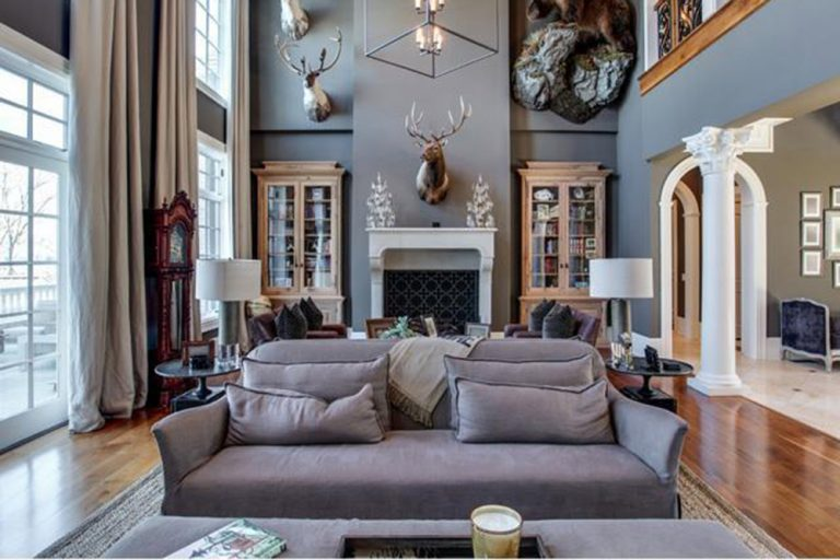 Gorgeous living room illuminated by a caged chandelier that hung over the gray couch. It has plum seats by the fireplace decorated with an antler head.