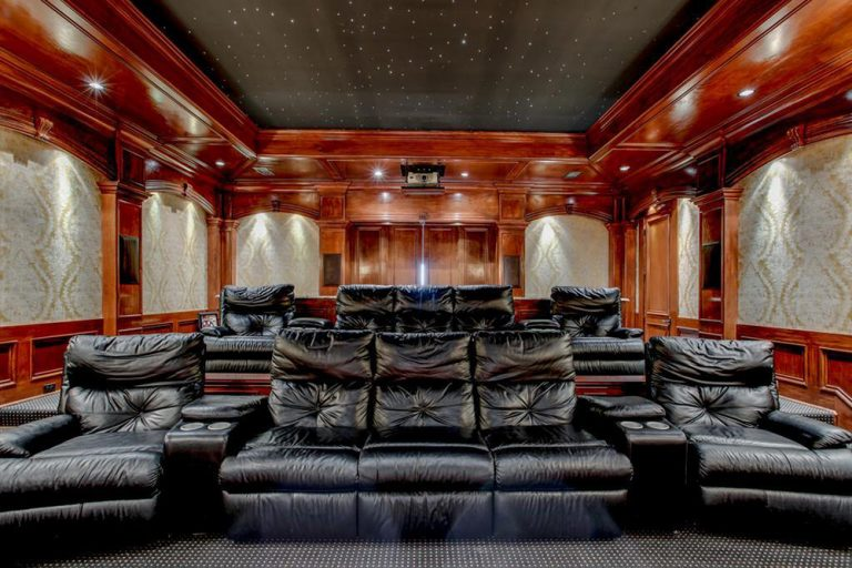 This home theater boasts elegant black sectional theater seats surrounded by reddish-finished accent and a charming black tray ceiling.